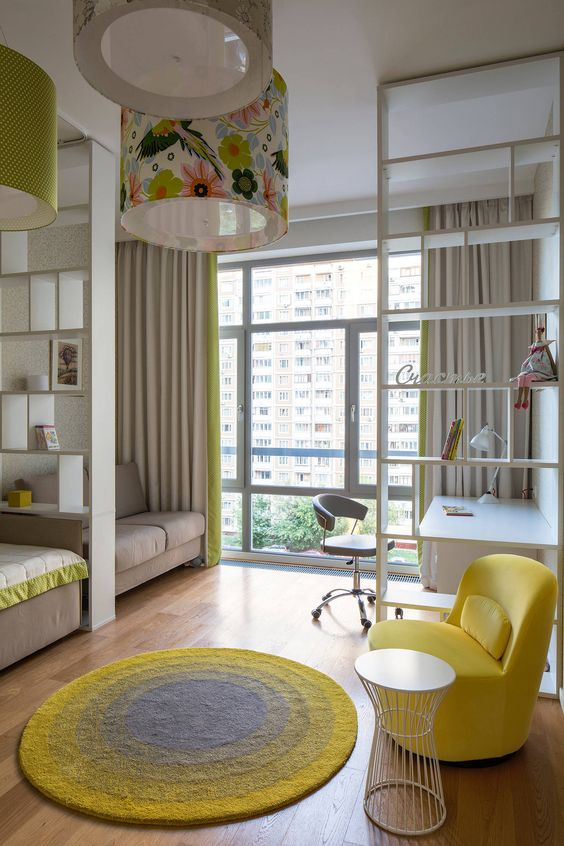 small apartment, wooden floor, brown sofa, white study table, office chair, beige curtain, shelves partition, yellow chair, bed, round yellow rug