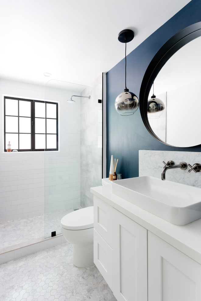 small bathroom dark blue wall round wall mirror glass pendant lamp white sink white floating vanity wall mounted faucet toilet white wall and floor tiles glass windows shower head