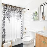 Small Bathroom Decorative Curtain White Wall Tiles Golden Light Fixtures Black Herringbone Floor Tile Toilet Wall Mirror Artwork Wooden Vanity Sink Built In Tub Rattan Basket