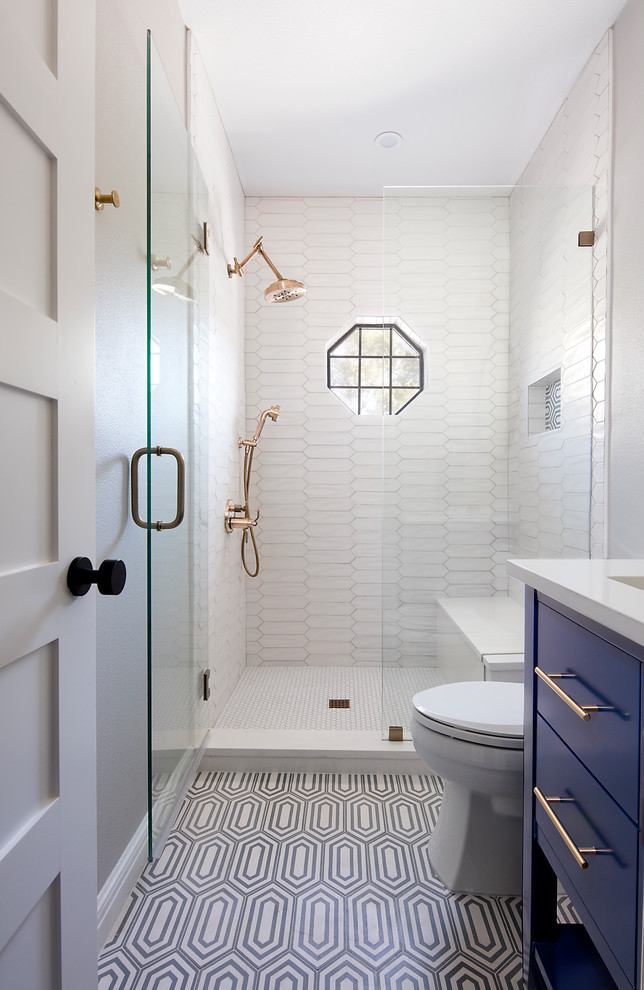 small bathroom glass window white floor and wall tiles blue vanity wall mirror gold shower fixtures glass shower doors toilet built in bench sink