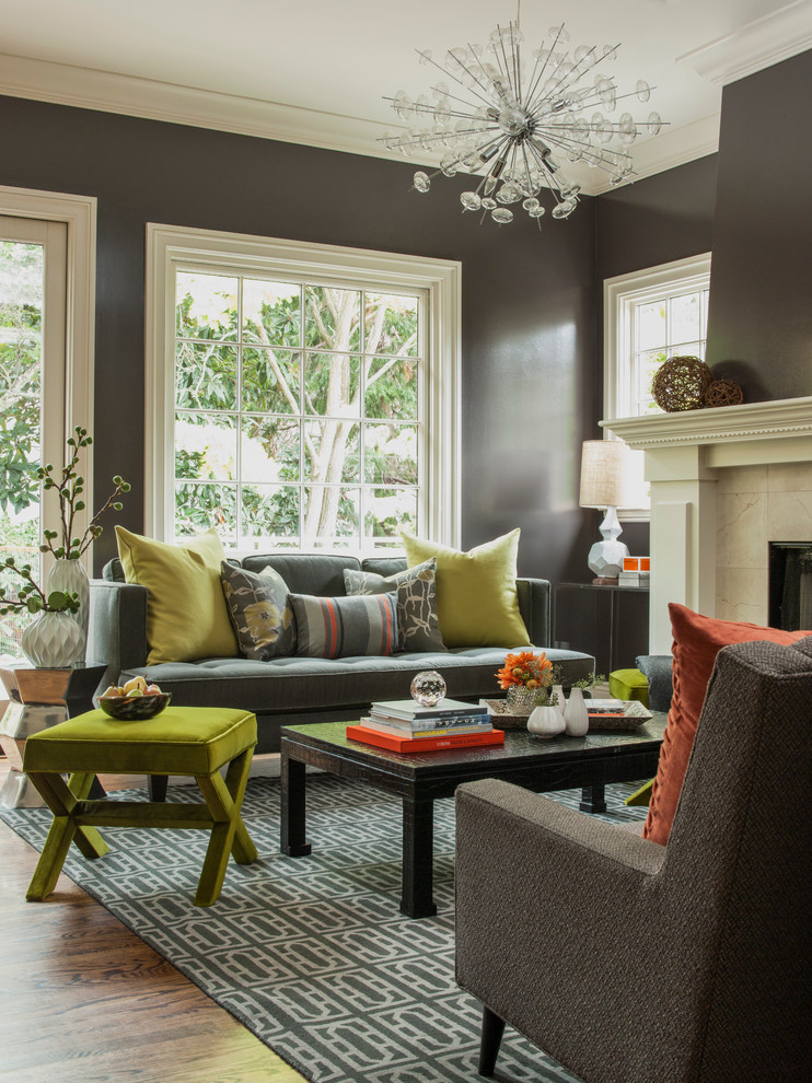 small living room design ideas dark gray walls glass window gray patterned rug black coffee table green stool gray sofas fireplce colorful pillows chandelier
