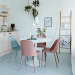 Small Open Kitchen With White Dining Table, Pink Blue Chairs, White Pendant, Wooden Cabinet, Wooden Kitchen Wall, White Wall, Wooden Rack, Blue Floor