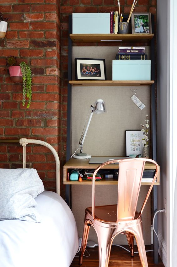 study in alcove, black steel shelves with wooden boards shelves, wooden table with drawer, copper chair, wooden floor, brick wall