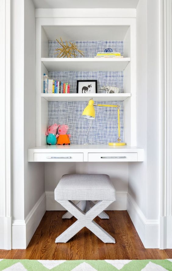 study in alcove, wooden floor, white wall, white built in shelves, white floating table, white ottoman, yellow table lamp
