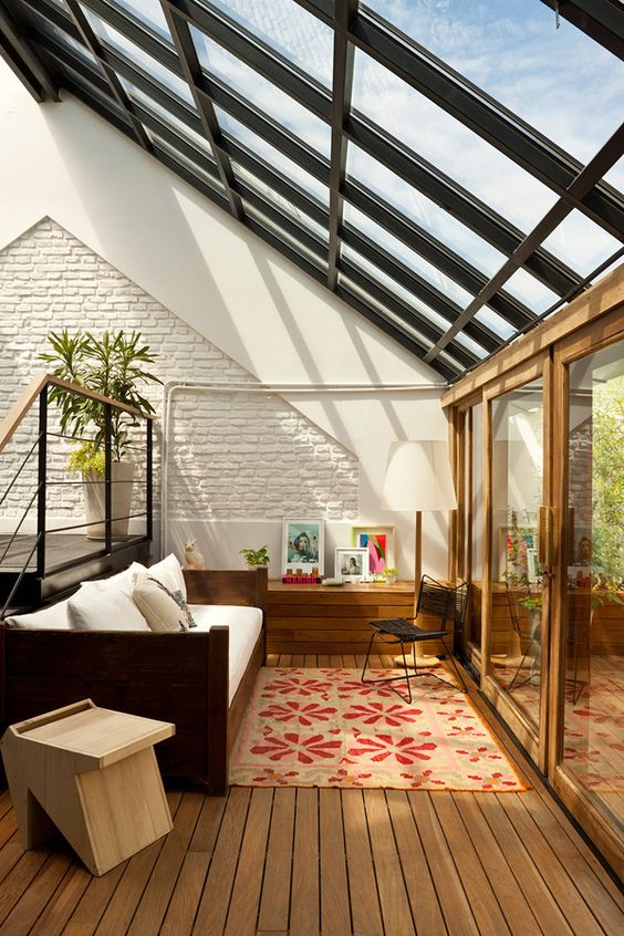 sun room, wooden floor, rug, wooden sofa with white cushion, sloping ceiling, clear glass ceiling and door
