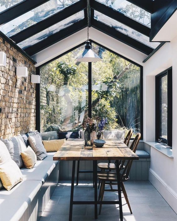 sun rooms, wooden floor, corner bench with cushion, open brick wall, white wall, clear glass wall and ceiling