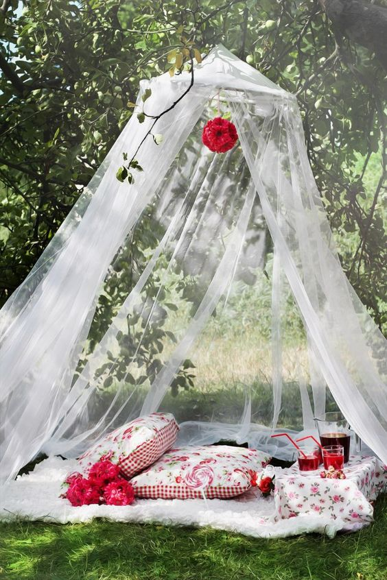 tent with white see through curtain, white rug, pillows