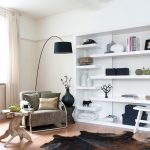 Unique Bookcase Beige Curtain Modern Armchair Cowhide Rug Black Floor Lamp Wooden Side Table Wooden Floor White Bench Stool Window Pillows Books Decorations