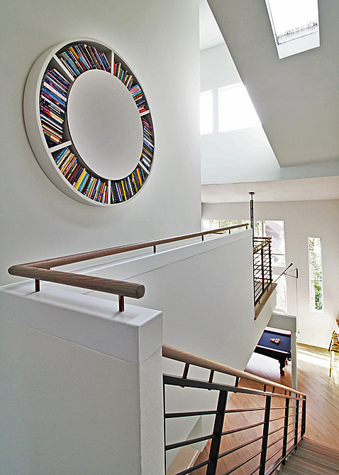 unique bookcase white spinning bookcase white railing wooden railing cap staircase white walls wndows skylights