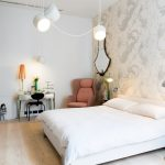 Vintage Bedroom Vanity Wall Mirror Wallpaper White Bedding Pink Pillows Wall Sconces White Pendant Lamps Black Cahair Table Lamps Bedside Table