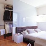 Walking Closet Behind The Headboard Bed, Glass Partition, Shelves And Rails, Wooden Floor,