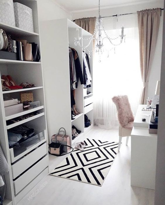 walking closet, two open cupboards, rails to hang clothes, shelves, drawers, white table, white chair, white floor, rug