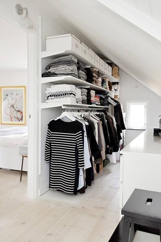 walking closet under sloping ceiling with white wooden shelves, rail to hang clothes under the shelves