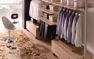 walking closet, wooden floor, open wooden shelves, rails to hang clothes, wooden drawer cabinet