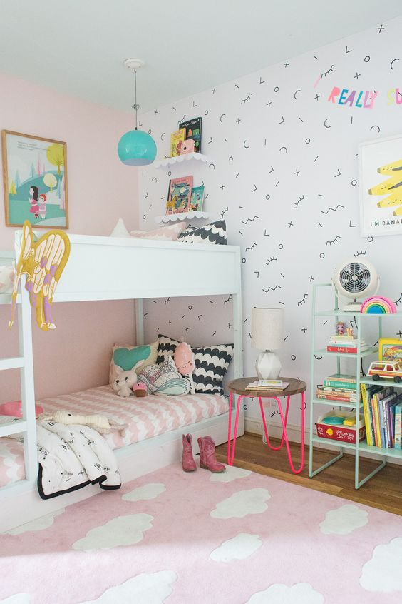 white bunk bed, wooden floor, pink rug, pink wall, white patterned wallpaper, green pendant, floating shelves, green wire shelves