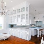 White Cabinet With Glass Door Wooden Floor Wooden Dining Table Chandelier White Chairs Blue Mosaic Backsplash White Island Stools Stove Sink Window
