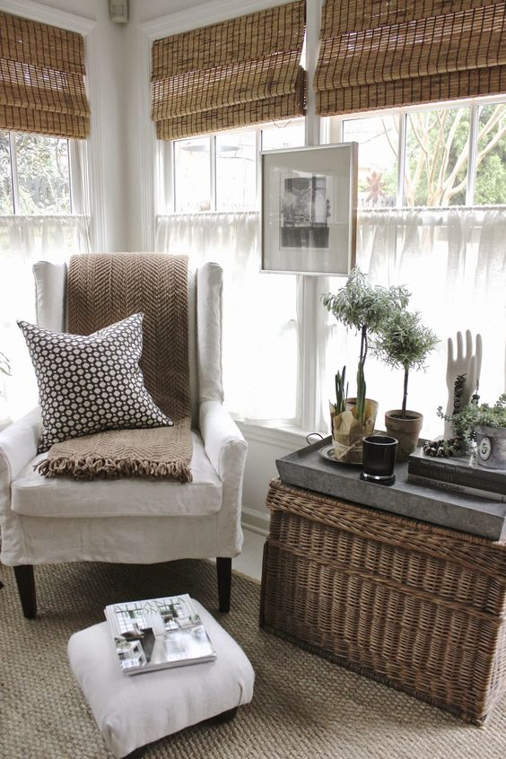 white cuhioned tall chair, rattan rug, rattan box as table, rattan shade
