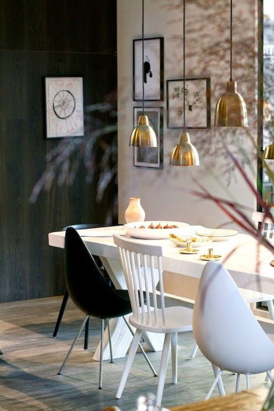white dining table with cross legs, black wall, white wall, golden pendants, white and black chairs, wooden floor