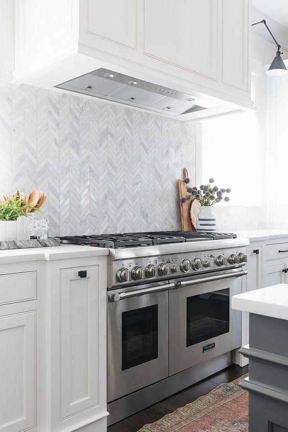 white grey chevron marble backsplash tiles, white upper bottom cabinet, silver stoves. grey island with white contertop