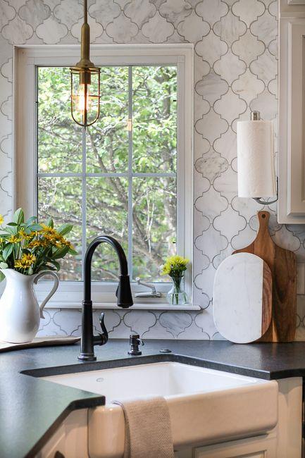 white marble arabesque backsplash, black countertop, white bottom cabinet, pendant, black faucet, white upper cabinet