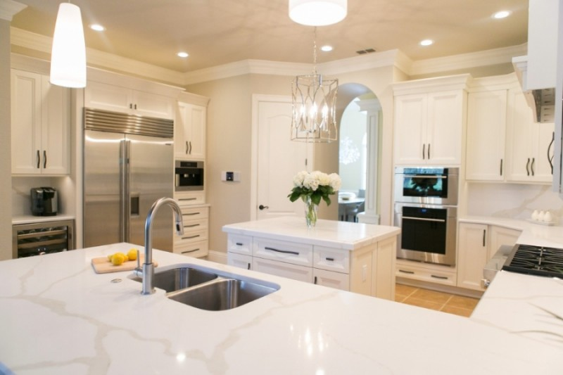 white marble kitchen backsplash, white upper and bottom cabinet, brown tiles, white counter top white pendants, chandelier, middle island