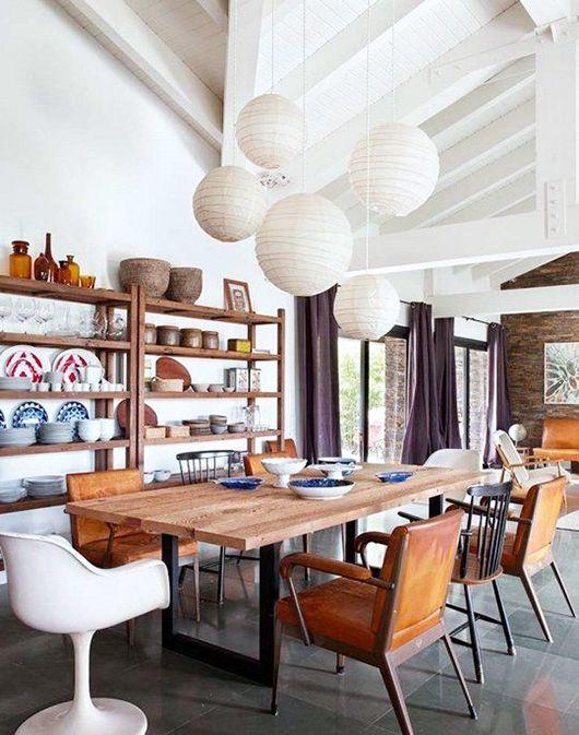 white paper moon pendants, wooden table, brown leather chairs, wooden chairs, white chairs, grey floor tiles, wooden shelves, white wall, white ceiling