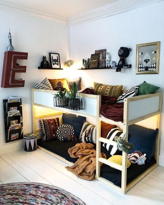 wooden bunk bed with boards on upper bed, white wall, wooden floor, rug, floating shelves