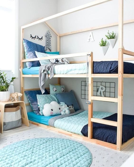 wooden bunk bed with house shaped frame on the upper, wooden floor, grey rug, round blue rug, side stool