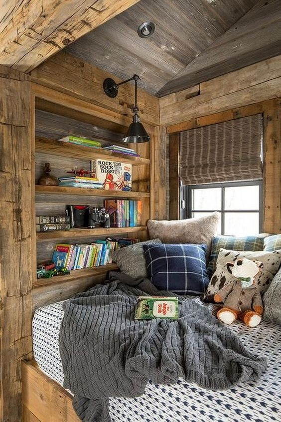wooden cabin, wooden window nook, built in shelves, wooden sloping ceilng, bed, pillows, black sconce