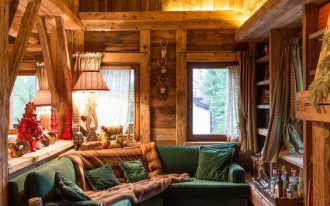 wooden cabine, wooden floor, open room, green corner sofa, green ottoman, wooden sheles, wooden side table