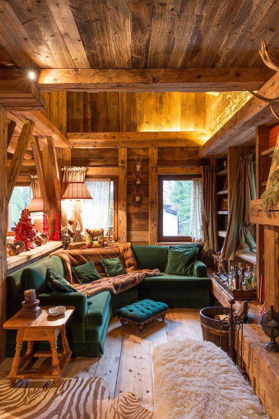 wooden cabine, wooden floor, open room, green corner sofa, green ottoman, wooden sheles, wooden side table