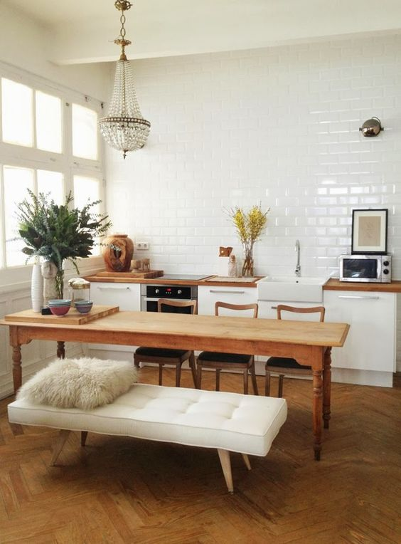 wooden chairs with black seating, wooden table, white tufted bench, wooden floor, cyrstal chandelier, white subway wall, white ceiling