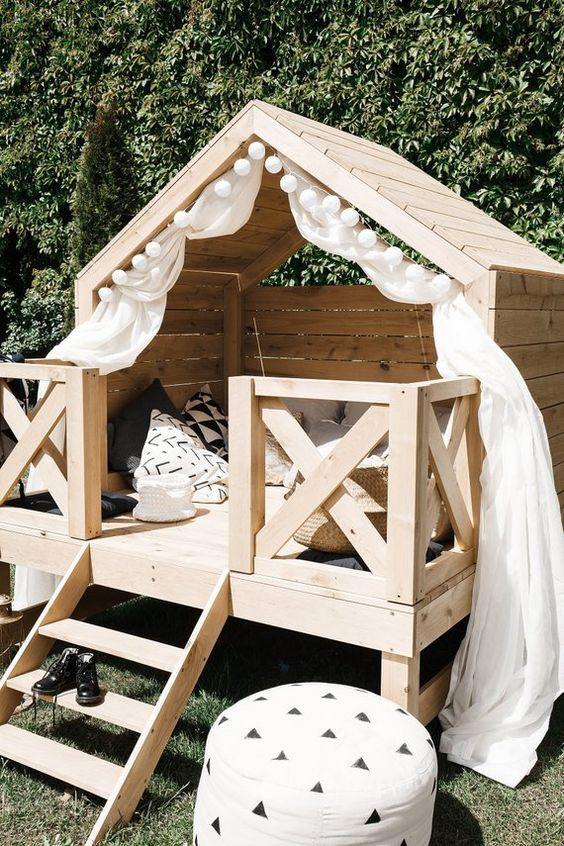 wooden garden tent with white curtain, cross fence, stairs, pillows, white ottoman