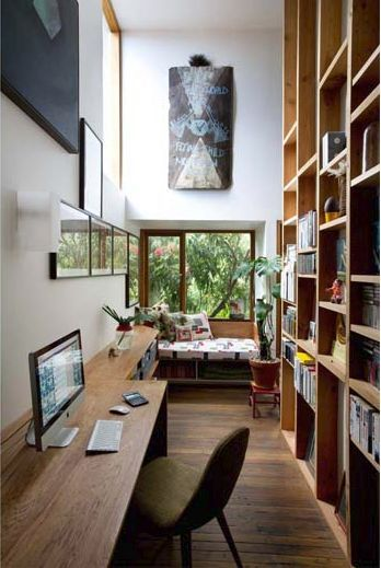 a long alley for study room, wooden floor, wooden long built in table, green chair, tal wooden shelves, white wall, window , reading nook