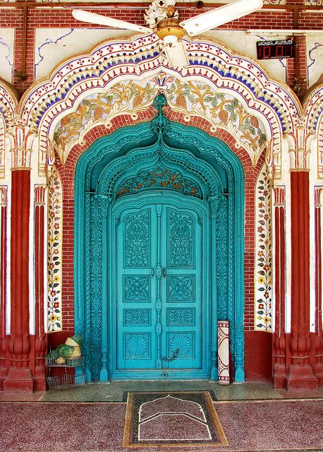 antique Moroccan doors in bright teal, red pillar, red pattern on the arch