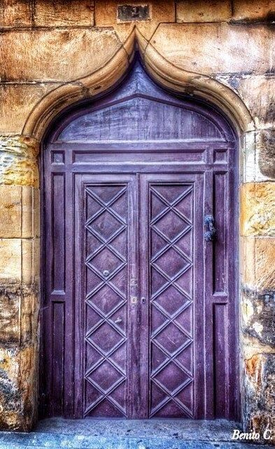 antique door in purple, sharp arch, yellow wall