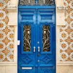Antique Doors With Blue Color, White Curvy Details, Orange Patterned Wall, Arch