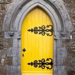 Antique Small Door In Yellow, Black Wrought Iron, Grey Cement Arch