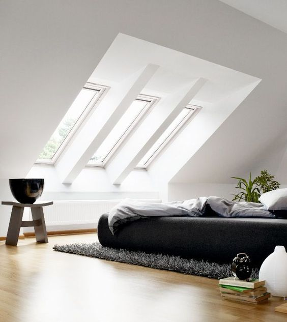 attic bedroom, wooden floor, windows on sloping ceiling, grey stool, black bed, grey rug