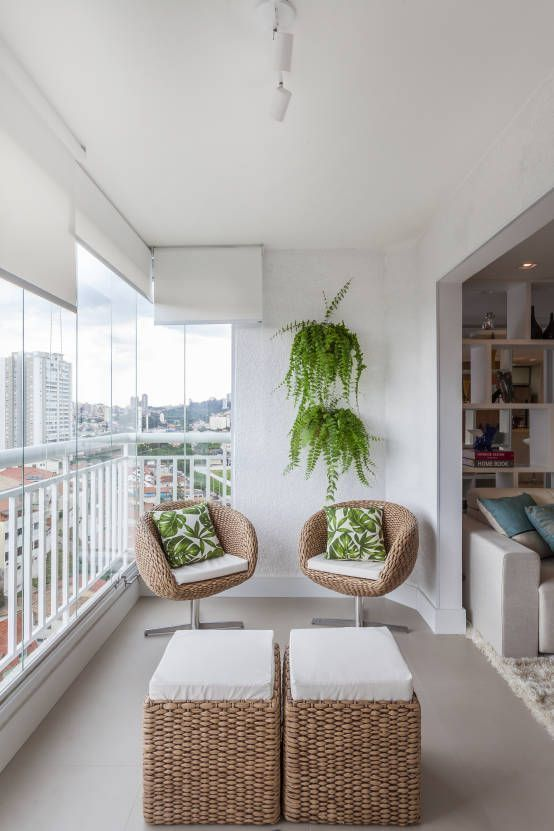 balcony, grey floor, white wall, rattan square ottoman with white cushion, rattan chairs with white cushion, hanging plants, white fence, rolling shade
