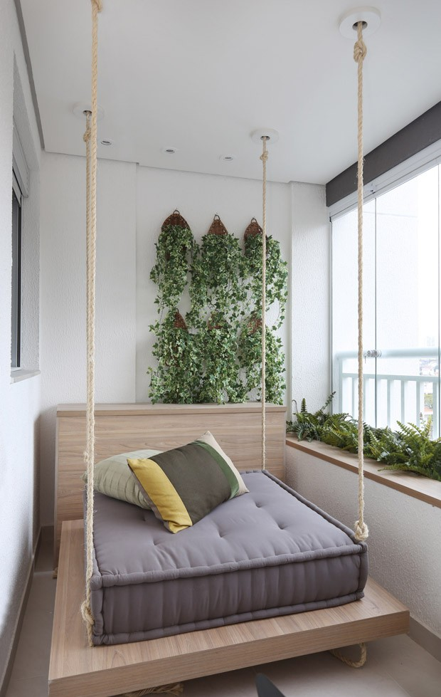 balcony, hanging wooden platform, grey cushion, pillows, white wall, plants on the fence and wall