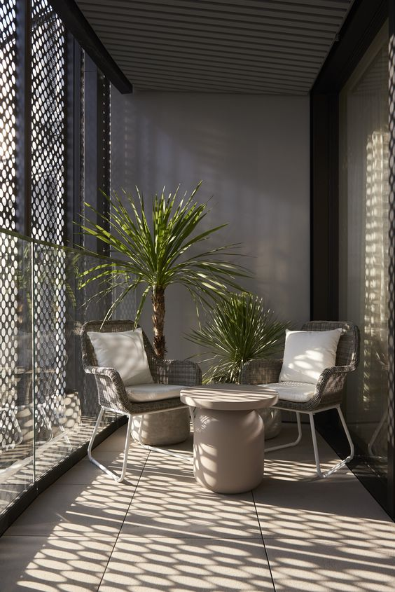 balcony, shade, brown floor tiles, grey rattan chairs, round coffee table, plants, grey wall