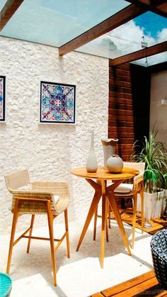 balcony, white textured wall and floor, round wooden table, wooden chair with rattan seat, wooden floor, clear glass ceiling