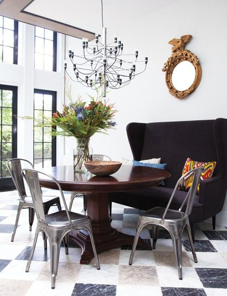 banquette, black high sofa, dark wooden round table, silver industrial chairs, checkered floor, chandelier, mirror