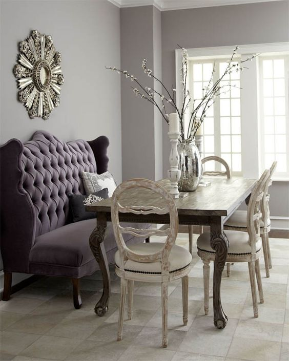 banquette, dark tufted sofa, white chairs, wooden table, grey wall, grey floor