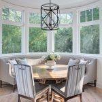 Banquette In The Alcove, Grey Round Sofa, Round Table, Grey Chairs, Chandelier, White Wooden Ceiling, Glass Window