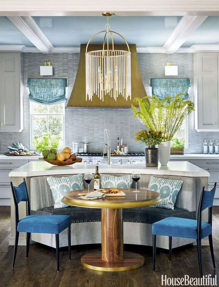 banquette in the kitchen, wooden floor, white bottom cabinet, grey island with white top, blue shade, chandelier, golden hood, blue sofa, blue chairs, golden round table