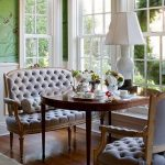 Banquette Near The Glass Window, Wooden Floor, Tufted Grey Sofa And Chairs, Wooden Table, White Table Lamp, Rug, Glass Window