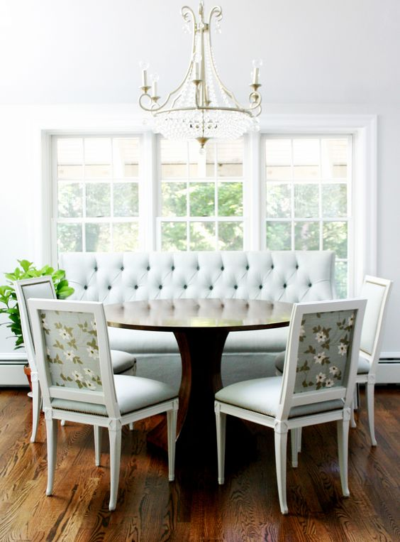 banquette, wooden floor, white wall, white tufted sofa, white chairs with flower pattern on the back, round wooden table, crystal chandelier