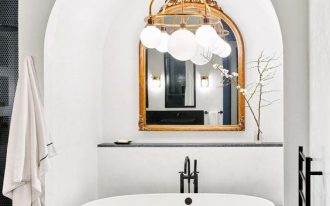 bathroom, black floor tiles, white tub under the white arch, white balls chandelier, black white chair
